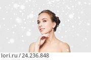 Купить «beautiful young woman touching her face over snow», фото № 24236848, снято 14 апреля 2016 г. (c) Syda Productions / Фотобанк Лори