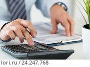 Мужчина считает на калькуляторе и сверяет цифры с документом. Стоковое фото, фотограф Людмила Дутко / Фотобанк Лори