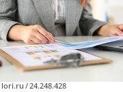 Купить «Деловая женщина с графиками сидит за столом», фото № 24248428, снято 26 мая 2016 г. (c) Людмила Дутко / Фотобанк Лори