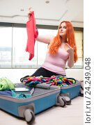 Young woman packing for travel vacation. Стоковое фото, фотограф Elnur / Фотобанк Лори