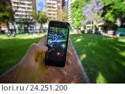 Приложение Покемон Go на экране смартфона в руке человека в летнем парке (2016 год). Редакционное фото, фотограф AK Imaging / Фотобанк Лори