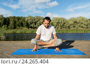 man making yoga in scale pose outdoors. Стоковое фото, фотограф Syda Productions / Фотобанк Лори
