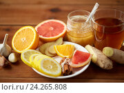 Купить «ginger tea with honey, citrus and garlic on wood», фото № 24265808, снято 13 октября 2016 г. (c) Syda Productions / Фотобанк Лори