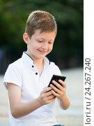 Купить «child playing with phone», фото № 24267240, снято 19 июня 2019 г. (c) Яков Филимонов / Фотобанк Лори