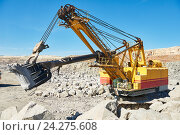 Купить «excavator works with granite or ore at opencast mining», фото № 24275608, снято 8 сентября 2016 г. (c) Дмитрий Калиновский / Фотобанк Лори