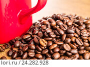 Красная кофейная кружка и обжаренные зёрна кофе. Стоковое фото, фотограф Михаил Аникаев / Фотобанк Лори