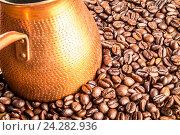 Турка для кофе в обжаренных кофейных зернах. Стоковое фото, фотограф Михаил Аникаев / Фотобанк Лори