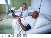 Купить «Doctor discussing x-ray with patient in ward», фото № 24295156, снято 11 сентября 2016 г. (c) Wavebreak Media / Фотобанк Лори