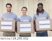 Купить «Three smiling volunteers holding donation boxes», фото № 24295932, снято 19 августа 2018 г. (c) Wavebreak Media / Фотобанк Лори