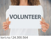 Купить «Woman holding a volunteer placard», фото № 24300564, снято 25 мая 2020 г. (c) Wavebreak Media / Фотобанк Лори