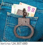 Полицейские стальные наручники и банкноты евро в заднем кармане джинсов, фото № 24307680, снято 4 декабря 2016 г. (c) FotograFF / Фотобанк Лори