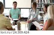 Купить «Discusses a group of people indoors», видеоролик № 24309424, снято 29 июля 2016 г. (c) Raev Denis / Фотобанк Лори