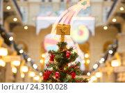 Купить «Наряженная новогодняя елка с декоративным фотоаппаратом на макушке стоит в ГУМе в преддверии Нового года в центре Москвы, Россия», фото № 24310028, снято 3 декабря 2016 г. (c) Николай Винокуров / Фотобанк Лори