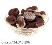 Купить «Шоколадные кофеты в стеклянной вазе, изолированно на белом фоне», фото № 24310296, снято 3 ноября 2016 г. (c) Литвяк Игорь / Фотобанк Лори