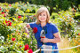 Woman gardening red roses and holding horticultural tools on sunny day, фото № 24311552, снято 17 июня 2016 г. (c) Яков Филимонов / Фотобанк Лори