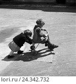 Купить «Zwei Kinder spielen mit einem Dreirad, Deutschland 1930er Jahre. Two children playing with a three wheeler, Germany 1930s.», фото № 24342732, снято 23 июля 2018 г. (c) mauritius images / Фотобанк Лори