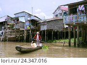 Купить «Vietnamese in the oar boat in front of simple building on stilts on the Mekong», фото № 24347016, снято 16 апреля 2014 г. (c) mauritius images / Фотобанк Лори