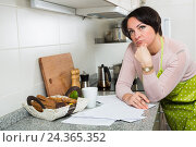 Купить «Sad middle aged housewife looking through bills», фото № 24365352, снято 21 октября 2018 г. (c) Яков Филимонов / Фотобанк Лори
