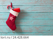 Купить «Christmas sock with gifts on wooden wall», фото № 24428664, снято 5 декабря 2016 г. (c) Майя Крученкова / Фотобанк Лори