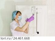 Купить «Медицинская сестра в маске и перчатках готовит капельницу для внутривенного вливания», фото № 24461668, снято 6 мая 2016 г. (c) Наталья Гармашева / Фотобанк Лори