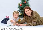 Купить «Мама с маленькой дочкой пишут письмо Деду Морозу рядом с елкой», фото № 24462896, снято 9 декабря 2016 г. (c) Гетманец Инна / Фотобанк Лори