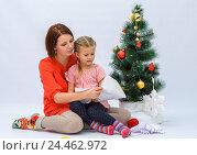 Купить «Мама с маленькой дочкой смотрят в конверт  с письмом Деду Морозу рядом с елкой», фото № 24462972, снято 9 декабря 2016 г. (c) Гетманец Инна / Фотобанк Лори