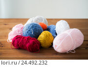Купить «knitting needles and balls of yarn on wood», фото № 24492232, снято 20 октября 2016 г. (c) Syda Productions / Фотобанк Лори