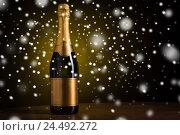 Купить «bottle of champagne with golden label over snow», фото № 24492272, снято 18 ноября 2015 г. (c) Syda Productions / Фотобанк Лори