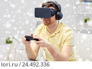 Купить «man in virtual reality headset with controller», фото № 24492336, снято 12 марта 2016 г. (c) Syda Productions / Фотобанк Лори