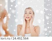 Купить «happy young woman looking to mirror at bathroom», фото № 24492564, снято 13 февраля 2016 г. (c) Syda Productions / Фотобанк Лори