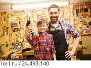 Купить «father and son with drill working at workshop», фото № 24493140, снято 14 мая 2016 г. (c) Syda Productions / Фотобанк Лори