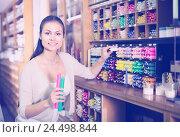 Купить «young woman picking candles in craft shop», фото № 24498844, снято 26 июня 2019 г. (c) Яков Филимонов / Фотобанк Лори
