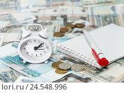 Купить «Российские деньги, часы- будильник, блокнот и ручка. Налоги и платежи», фото № 24548996, снято 9 декабря 2016 г. (c) Наталья Осипова / Фотобанк Лори