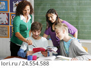 Купить «Schoolboys, schoolgirl, teacher, consider, books, smile, look at classroom, at school desk, art books, painting implements, cheerfully, happy, lessons...», фото № 24554588, снято 1 октября 2009 г. (c) mauritius images / Фотобанк Лори