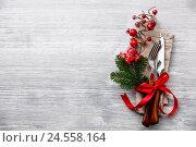 Купить «Столовые приборы с новогодними украшениями на сером деревянном фоне», фото № 24558164, снято 10 декабря 2016 г. (c) Лисовская Наталья / Фотобанк Лори