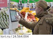Купить «Молодая женщина взвешивает овощи в гипермаркете», фото № 24564004, снято 11 декабря 2016 г. (c) Юлия Юриева / Фотобанк Лори