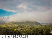 Биробиджанская телебашня высотой 234 метра, построенная в 1972 году. Сопка в тумане (облаках) (2012 год). Стоковое фото, фотограф Евгений Беляев / Фотобанк Лори