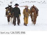 Купить «Cowgirl and cowboy walking beside their Quarter Horses through the snow,», фото № 24595996, снято 21 июля 2018 г. (c) mauritius images / Фотобанк Лори