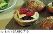 Купить «Cooking hamburger. A pieces of cucumber putting on the bun with the cutlet, cheese, tomato. HD», видеоролик № 24690716, снято 12 декабря 2016 г. (c) ActionStore / Фотобанк Лори