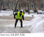 Рабочий коммунальной службы чистит дорогу от снега на Байкальской улице в Гольянове в Москве (2012 год). Редакционное фото, фотограф lana1501 / Фотобанк Лори