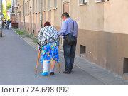 Купить «Пожилая женщина со сломанной ногой на костылях в сопровождении мужчины», фото № 24698092, снято 12 мая 2016 г. (c) Михаил Рудницкий / Фотобанк Лори