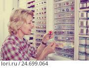 Купить «Female next to shelf with buttons», фото № 24699064, снято 23 мая 2019 г. (c) Яков Филимонов / Фотобанк Лори