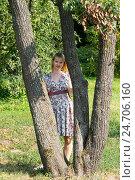 Купить «Девушка стоит между деревьями солнечным летним днем», фото № 24706160, снято 10 августа 2014 г. (c) Андрей Некрасов / Фотобанк Лори