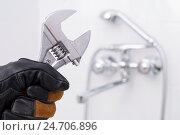 Купить «Разводной ключ в руке на фоне смесителя», фото № 24706896, снято 5 февраля 2006 г. (c) Myroslav Kuchynskyi / Фотобанк Лори
