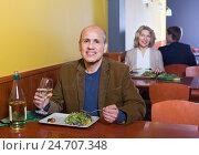 Купить «Happy positive smiling mature male having meal with wine», фото № 24707348, снято 21 июля 2018 г. (c) Яков Филимонов / Фотобанк Лори
