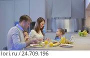 Купить «Smiling parents with children at home», видеоролик № 24709196, снято 19 сентября 2019 г. (c) Raev Denis / Фотобанк Лори