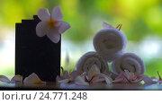 Купить «Slow motion view of falling petals of flowers against green blurred background on the table with flower Plumeria and towels», видеоролик № 24771248, снято 28 сентября 2016 г. (c) Данил Руденко / Фотобанк Лори