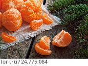 Купить «Очищенные мандарины на деревянном фоне», фото № 24775084, снято 20 ноября 2016 г. (c) Виталий Федоров / Фотобанк Лори