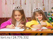 Купить «Две девочки радостно пишут письмо деду морозу сидя за столом в домашней обстановке», фото № 24776332, снято 25 декабря 2016 г. (c) Иванов Алексей / Фотобанк Лори