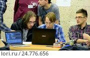 Купить «Студенты всматриваются в экран монитора ноутбука во время выполнения задания и общаются между собой», видеоролик № 24776656, снято 26 декабря 2016 г. (c) FMRU / Фотобанк Лори